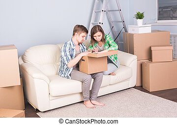 Home, people and moving concept - young couple looking for something in a box sitting on sofa