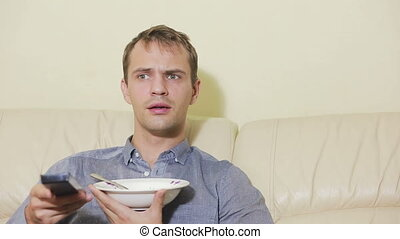 man with remote control watching tv at home