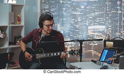 Home recording studio: young vocalist rehearsing by singing in microphone and playing guitar
