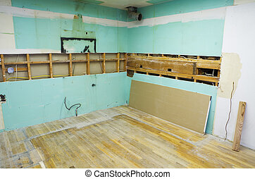 a kitchen near the start of a home remodel with all of the cabinets and appliances removed