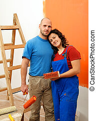 Home renovation - Young happy couple painting their new home...