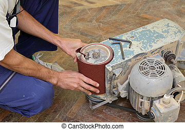 Home renovation - Worker fixing grinding machine for parquet...