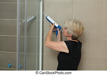 Home renovation, shower cabin fixing with silicone - Woman ...