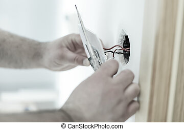 home renovation - Man installing light switch after home...