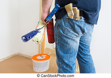 home renovation - Man holding rollers and brushes while...