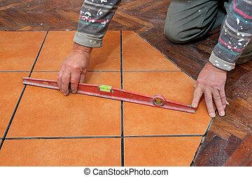 Home renovation tiles - Home renovation, worker levelling...