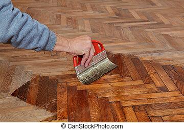 Home renovation - Varnishing of oak parquet floor, workers...