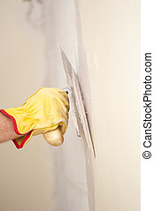 Closeup of palette-knife or scraper and cement filling for house renovation construction in hands of handyman and worker fixing interior wall, with blurred background and copy space.
