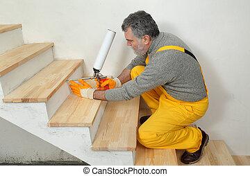 Home renovation, wooden stairs fix with polyurethane spray gun