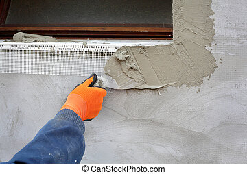 Home renovation - Worker spreading mortar over styrofoam ...