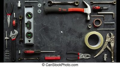 Home repair concept stop motion animation of work tools on a dark background. Top view, flat lay