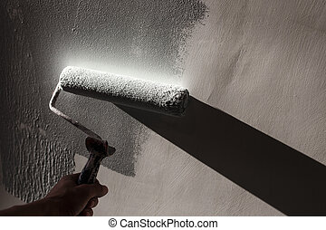 Home repairs. Painting the walls of the room in gray with a paint roller