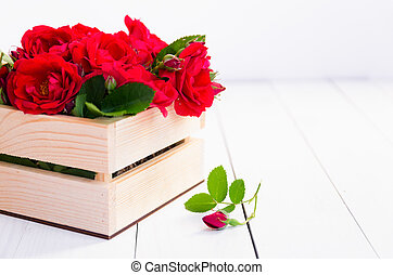 Home roses in a wooden box on a white wooden table. With copy space