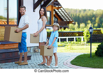 Home - Smiling family with boxes by the house