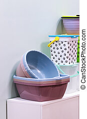 Home space organization, many different plastic household goods for storage and cleaning, selection of new clean washbowl, convenient containers with a lid on the shop window