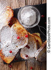 Home sweet tasty toast with powdered sugar and cranberries macro on the table. Vertical top view