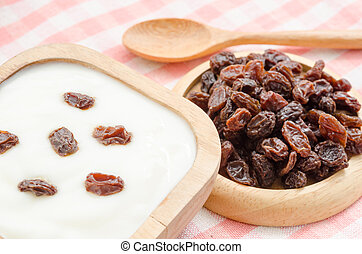 Home sweet yogurt with raisins in a wooden bowl with fower on fabric background.