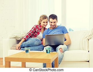 smiling couple with laptop computer at home