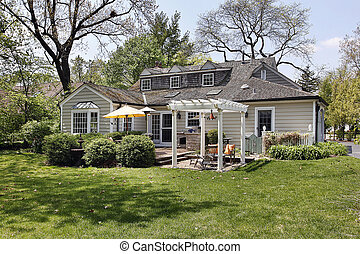 Rear view of suburban home with pergola