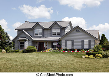 Home in suburbs with gray siding and covered entry