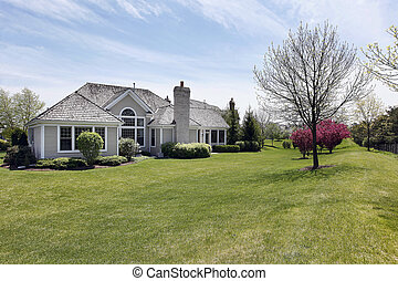 Rear view of suburban home with large back yard
