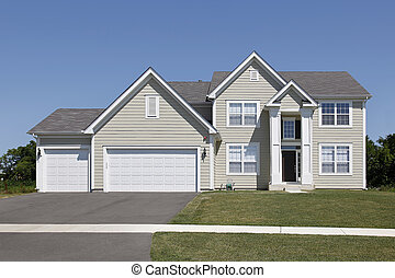Suburban home with tan siding and arched entry