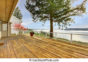 Large wood porch with glass railings and water view.
