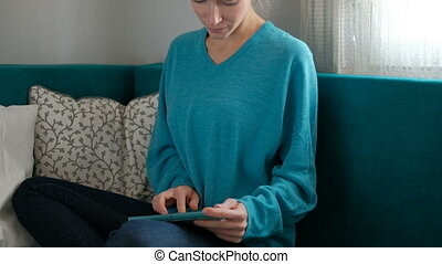 Home working of Woman blond sitting on sofa with tablet