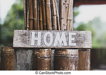 Home written on wooden sign surrounded by bamboo