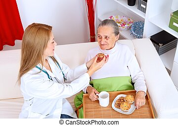 Homecare - Lovely nurse helping old woman eating cookies