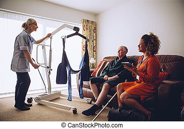 Homecare Workers preparing Hoist - Two homecare nurses at an...