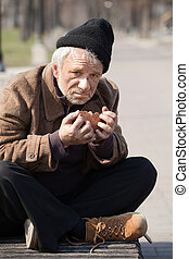 Homeless and hungry. Close up of depressed senior man eating...