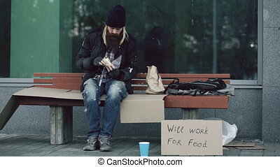 Homeless and jobless american man with cardboard sign eat...