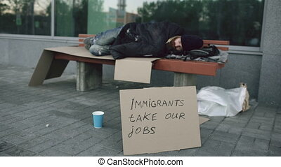 Homeless and jobless european man with cardboard sign sleep...