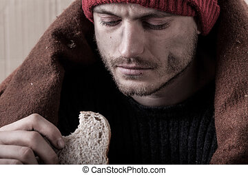 Homeless and poor man eating sandwich, horizontal