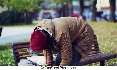 Homeless beggar man outdoors in park. - A portrait of...