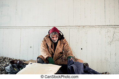 Homeless beggar man sitting outdoors in city asking for money donation.