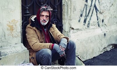Homeless beggar man sitting outdoors in city asking for...