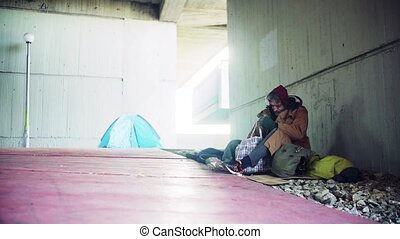 Homeless beggar man sitting outdoors in city, putting things...