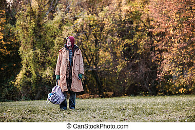 Homeless beggar man standing outdoors in park, holding bag. Copy space.