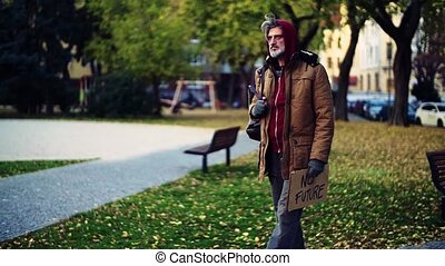 Homeless beggar man walking outdoors in park. Slow motion...