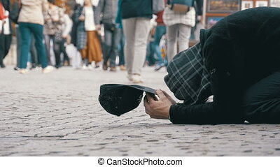 Homeless Beggar Man with a Hat on the Sidewalk Begs for Alms...