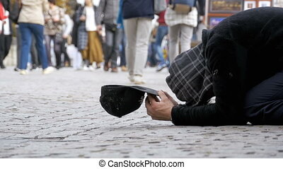 Homeless Beggar Man with a Hat on the Sidewalk Begs for Alms from People Passing by. Slow Motion
