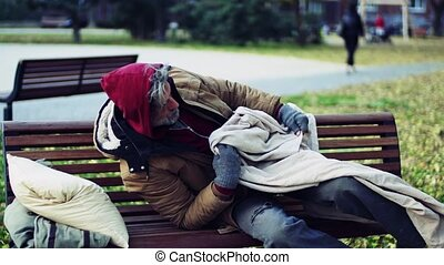 Homeless beggar man with a pillow lying down on bench...