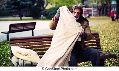 Homeless beggar man with a pillow lying on bench outdoors in...
