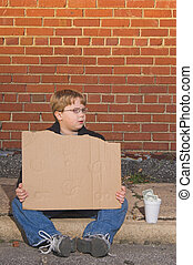 Homeless Boy - A homeless boy with a blank cardboard sign.