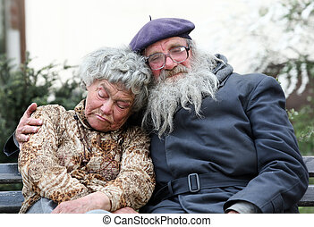 Homeless couple - An old homeless couple sleeping on a bench