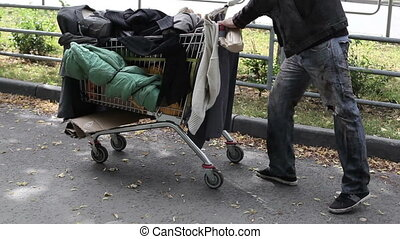 Homeless guy with a limp pushing a shopping cart full of dirty clothes