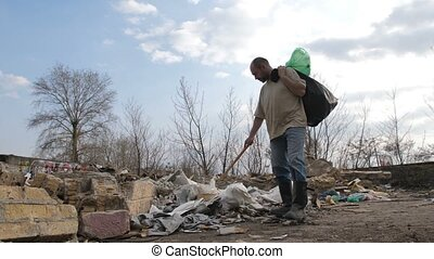 Homeless male searching for plastic at trash site - Front...