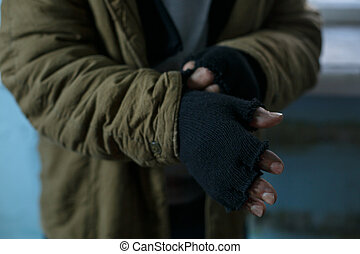 Homeless man fixing his gloves.
